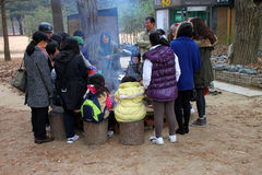 Travel in Naminara republic, Korea. NAMINARA REPUBLIC, KOREA - NOVEMBER 26 : The unidentified group of tourists are sitting and some standing around fireplace on royalty free stock photography