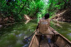 Travel by native style canoe in africa forest Royalty Free Stock Photography