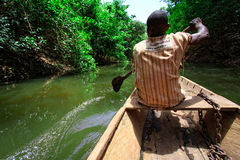 Travel by native style canoe in africa forest Royalty Free Stock Photo