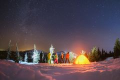 Travel night camping winter concept with friends and tent. Group of five friends with tent is enjoying beautiful night landscape against mountains, stars and Royalty Free Stock Photos