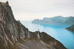 Travel Norway vacations man standing alone on cliff. Above fjord adventure lifestyle solitude silence concept scandinavian climbing outdoor stock image