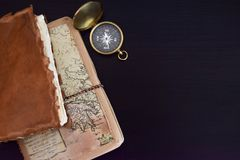 Travel Notes and Compass. Old travel notebooks and compass placed on black wood surface Royalty Free Stock Photo