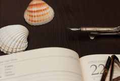 Travel Notes. Glasses, ink pen and notebook on wooden table with sea shells Stock Image