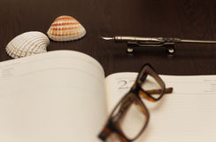 Travel Notes. Glasses, ink pen and notebook on wooden table with sea shells Stock Photo