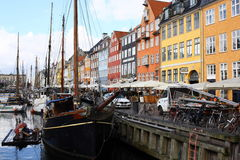 Travel in Nyhavn of Denmark. Travel in Nyhavn Port of Denmark in Spring. The weather is great with some cloud. You can find many ships and restaurants in this Stock Image