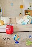 Travel objects. Sofa with map, pillow and globe, airline tickets, flipflops and suitcase near by Royalty Free Stock Photography