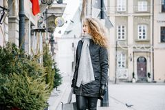 Travel the old city. A young woman travels. Market Square in Warsaw. Curly girl walks through the streets of the city. Poland Stock Images