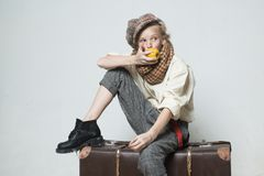 Travel with old suitcase. Homelss. old fashioned child in beret eat apple. retro fashion model. Vintage suspender. teen. Girl in retro male suit. street kid royalty free stock photos