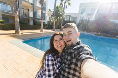 Travel, people and holiday concept - Happy couple taking selfie near a pool.  stock image