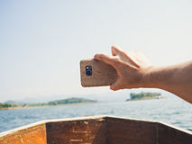 Travel photo with smartphone on longtail boat. Taking photo with smartphone while travel with longtail boat Stock Photography