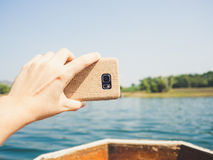 Travel photo with smartphone on longtail boat. Taking photo with smartphone while travel with longtail boat Stock Image