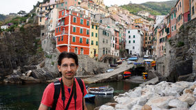 Travel photographer with on the background Riomaggiore village, the UNESCO World Heritage site of Cinque Terre, Italy, Europe Royalty Free Stock Photo