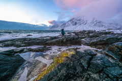 Travel photographer doing pictures outdoor at evening time. Lofoten islands. Beautiful Norway landscape. Stock Image