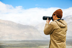 Travel photographer journalist holding a dslr camera in mountain background Royalty Free Stock Photo