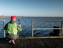 Travel photographer on pier. Photo shooting during sunny autumnal afternoon Royalty Free Stock Images