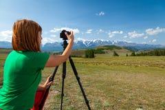 Travel photographer taking nature photo. Of mountain landscape. Hiker tourist professional woman on adventure vacation shooting slr camera on tripod stock photos
