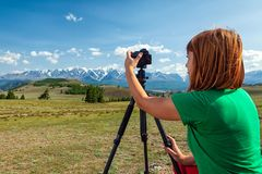 Travel photographer taking nature photo. Of mountain landscape. Hiker tourist professional woman on adventure vacation shooting slr camera on tripod royalty free stock photography