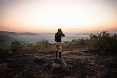 Travel photographer taking a shots at sunrise. Hipster with a little camera in the good light stock photos