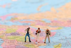 Travel photographers. Beautiful shot of travel photographers while standing on world map stock images