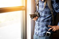 Travel and photography concept. photographer with backpack. And digital camera standing near window ready to travel for take photo , anonymous face. film effect royalty free stock photography