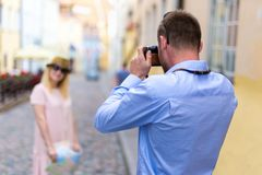 Travel and photography concept - young man taking photo of his w. Travel and photography concept - young men taking photo of his girlfriend or wife royalty free stock images