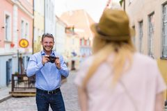 Travel concept - young man taking photo of his wife in old town. Travel and photography concept - young men taking photo of his wife in old town royalty free stock image