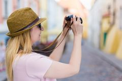 Travel and photography concept - young woman tourist walking wit. Travel and photography concept - young woman tourist walking in city with camera royalty free stock image