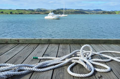 Sailing rope on a wharf pier with boats in the bac Stock Photo
