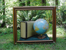 Travel Picture. A wood picture frame sets off a suitcase and a globe from the surrounding green foliage royalty free stock image
