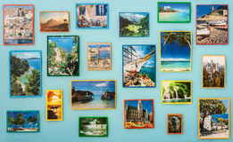 Travel-pictures of different size cut out of magazines and glued to blue wall. Stock Image