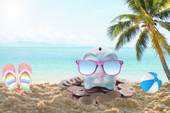 Travel piggy bank with sunglasses relax on the beach holiday. Royalty Free Stock Image