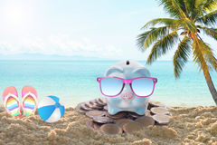 Travel piggy bank with sunglasses relax on the beach holiday. Stock Images