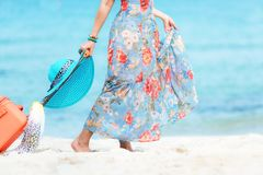 Travel Plan. Hand women traveler holding orange luggage walking on the beach. Traveler and Tourism planning trips summer vacations. Travel Plan. Hand woman royalty free stock image