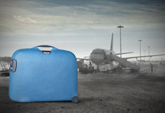 Travel by plane. Blue trolley case with airport in the background Stock Image