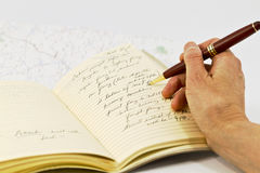 Travel Planning. Open journal with travel planning notations and map beneath book Royalty Free Stock Image