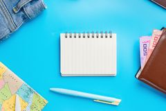 Travel Planning accessories, Airplane, wallet,sun glasses, money. Note pad, jeans, action camera,world map and passport with blank space on blue background Royalty Free Stock Photography
