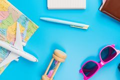 Travel Planning accessories, Airplane, wallet,sun glasses, money. Note pad, jeans, action camera,world map and passport with blank space on blue background Royalty Free Stock Images