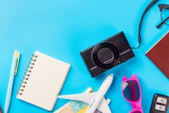 Travel Planning accessories, Airplane, wallet,sun glasses, money. Note pad, jeans, action camera,world map and passport with blank space on blue background Stock Images