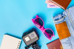 Travel Planning accessories, Airplane, wallet,sun glasses, money. Note pad, jeans, action camera,world map and passport with blank space on blue background Royalty Free Stock Image