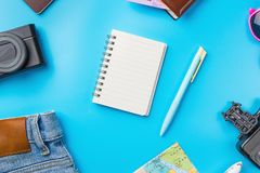 Travel Planning accessories, Airplane, wallet,sun glasses, money. Note pad, jeans, action camera,world map and passport with blank space on blue background Royalty Free Stock Photo