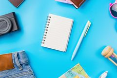 Travel Planning accessories, Airplane, wallet,sun glasses, money. Note pad, jeans, action camera,world map and passport with blank space on blue background Royalty Free Stock Photos