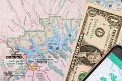 Travel planning with smart phone and travel map, detail of Arizona, USA map, Lake Powell, one Dollar bill. Travel planning with accessories, smart phone and royalty free stock image