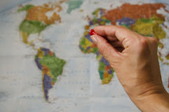 Travel planning. Hand with a pin pointing at a world map Stock Photography