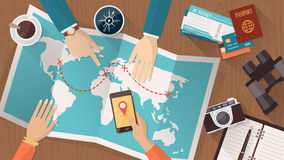 Travel planning. People planning a trip around the world, they are pointing on a map and using an app on a mobile phone, travel and vacations concept Stock Photo