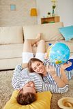 Travel planning. Restful couple with globe discussing where to spend summer while lying on the floor by sofa at home Stock Photos