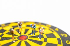 Travel, Planning and target Concpet. Close up of group of traveler miniature figures people with backpack standing on black and. Yellow dart board on white royalty free stock photos