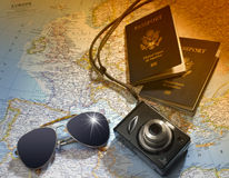 Travel plans. Two US American passports, camera and sunglasses over map of europe Stock Images