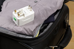 Travel power adapter with connectors for european, UK, and US po. Wer plugs on packed suitcase with clothings - travel preparation Royalty Free Stock Photography