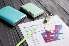 Travel preparation concept with insurance and cards on wooden table Royalty Free Stock Images