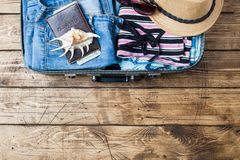 Travel preparations concept with suitcase, clothes and accessories on an old wooden table. Top view Copy space royalty free stock images